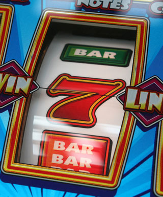 "A view of one reel on a classic slot machine showing the ""bar"" symbol and a 7."